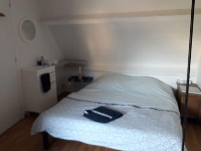 Lit, coin lavabo et wc à l étage du duplex indépendant