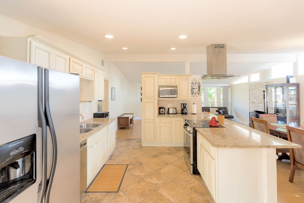 Kitchen with open floor plan tile floors with granite counters and high ceilings.