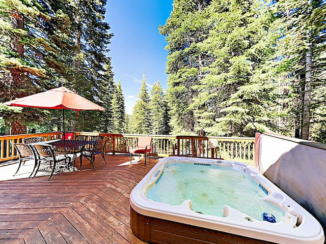 The expansive back deck features a built-in outdoor hot tub and table seating for six.