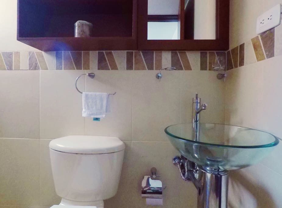 Private bathroom with shower, hot water, toilet, sink, mirror, cabinet and ventilation window