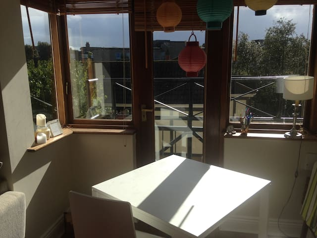 A sunny dinning table with a balconey