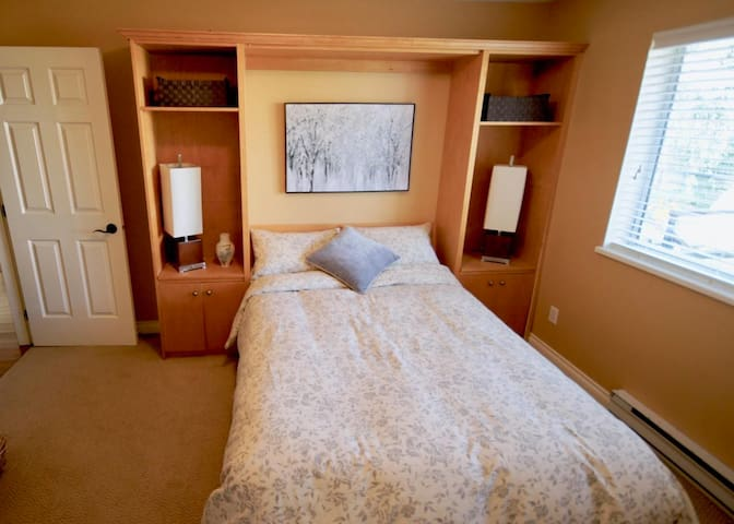 double bed , wall bed with work station in the room.
