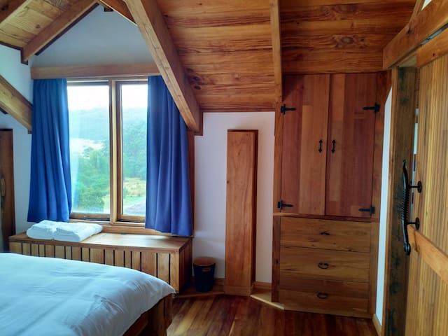The guest room features a queen size bed with high quality linen and hand crafted cabinetry