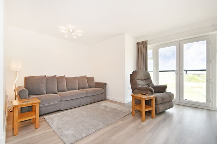This light airy lounge has a double sofa bed, and reclining Lazyboy rocking chair.  Two coffee tables, and some lovely LED lights.  The flooring is parquet laminate with a good size rug.