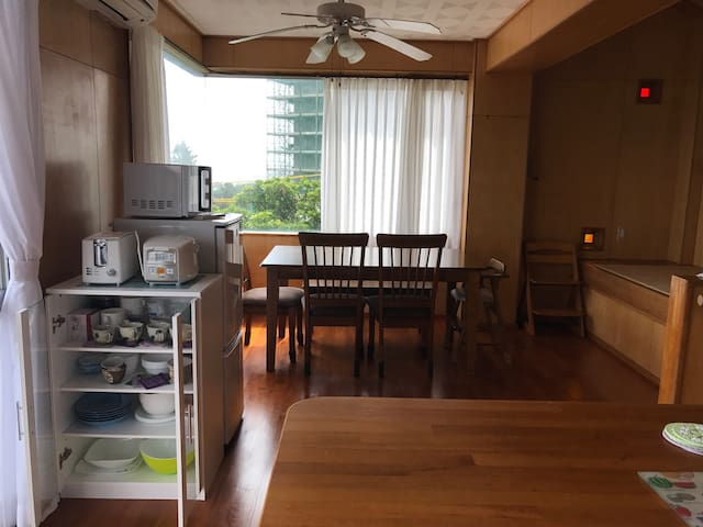 キッチンと食卓の間に食器棚や冷蔵庫、炊飯器、トースター、電子レンジ