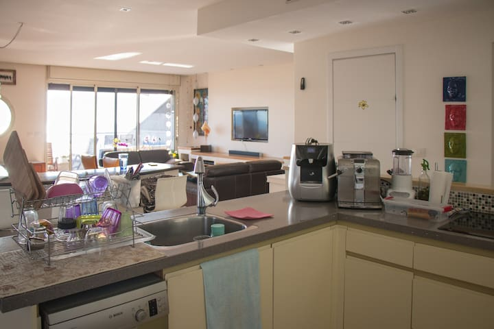 A fully equipped kitchen with induction stove, dishwasher and a big sink