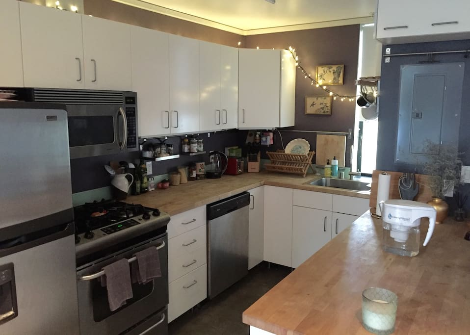 kitchen with butcher block counters, full fridge, stove, microwave, toaster, coffee, and more.