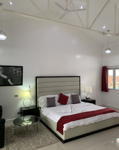 Bedroom with high ceiling and king size bed.