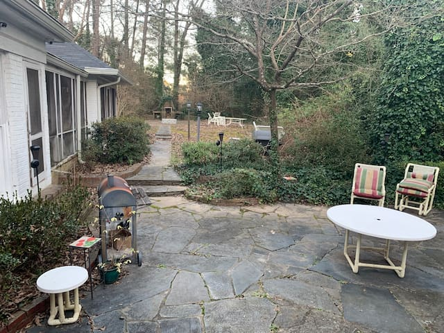 Patio area with charcoal grill, seating and dining area, and fire pit