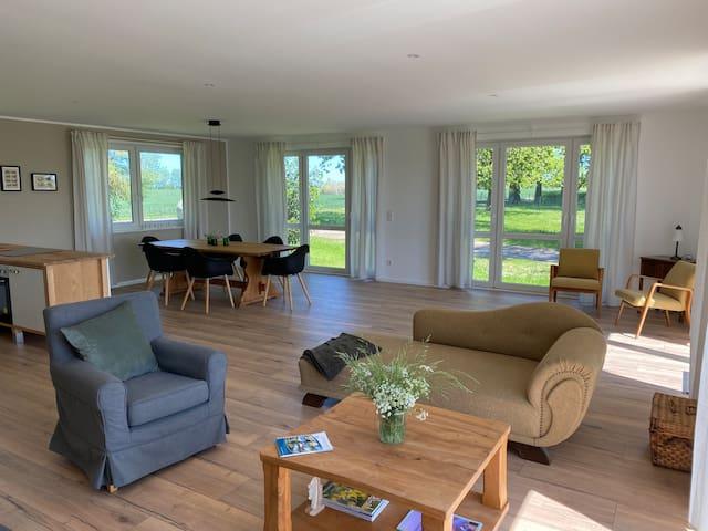 Der Wohn- und Essbereich mit offener Küche und weitem Blick über die Felder