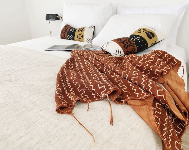 Wake up to beautiful morning light and savor a delicious cup of coffee in the fresh, open master bedroom that features a queen size bed, organic cotton linens, and original traditional African textiles.
