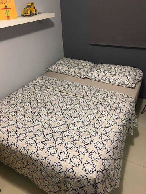 Cama de casal com protetor de colchão lençol e sobre lençol, travesseiros com protetor.