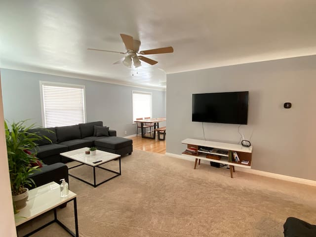 """Living room with large couch, marble coffee table, 50"""" Vizio SmartTV with Netflix & other free programming. Some books and boardgames for your enjoyment."""