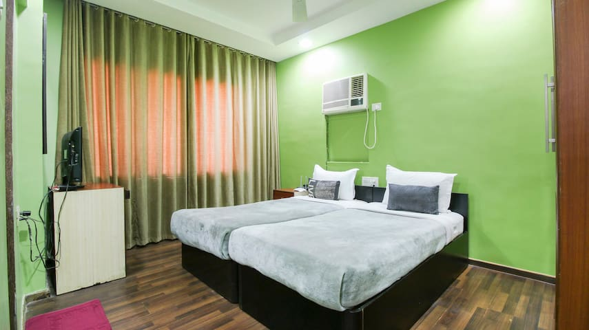 Two single beds (joined together, but can be separated, if desired). Flat-screen TV on left. Window air-conditioner provided.