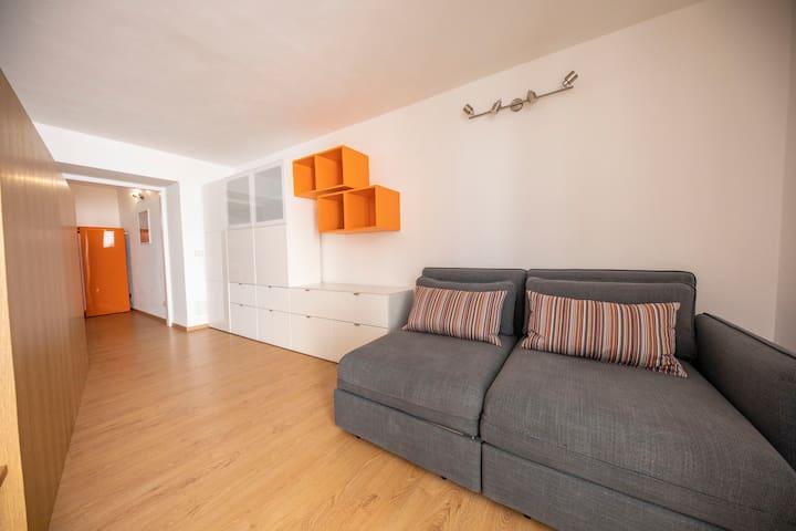 Living room con angolo TV, divano e letto matrimoniale