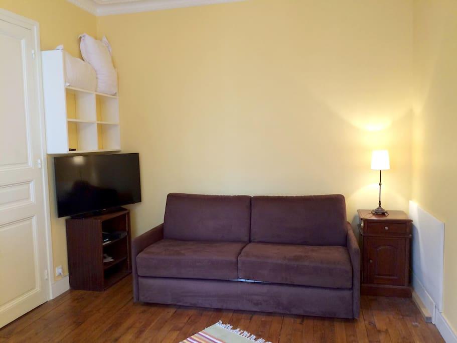 """Le canapé lit est très simple d'utilisation. TV 40"""" 102cm. Une chambre à la couleur chaleureuse, haute de plafond, aux meubles chinés"""