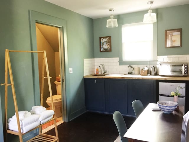View from seating area of kitchenette and bathroom. There's a table for two as well - to work from or enjoy ordering in for the night.