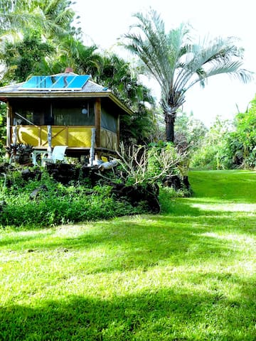 Hawaii vacation rental bali hut on an oceanfront acre of lawn and exotic tropical plants. Eco Friendly - solar power.