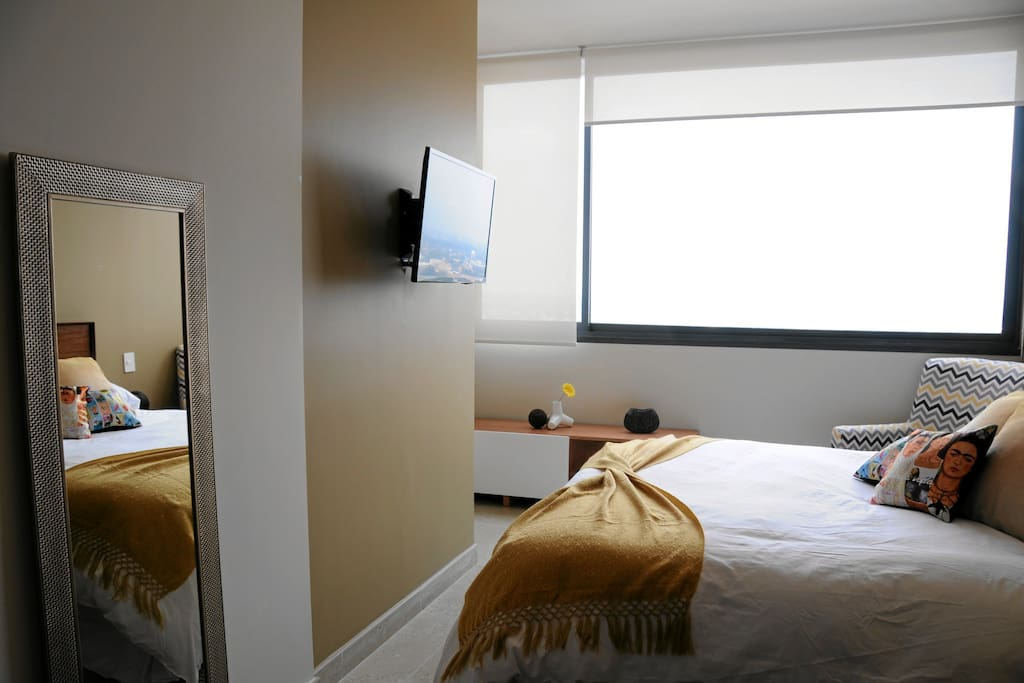 Master bedroom with flat screen TV and full size mirror.