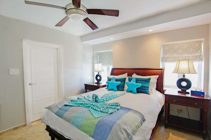 The second bedroom with a queen bed, en suite, and air-conditioning