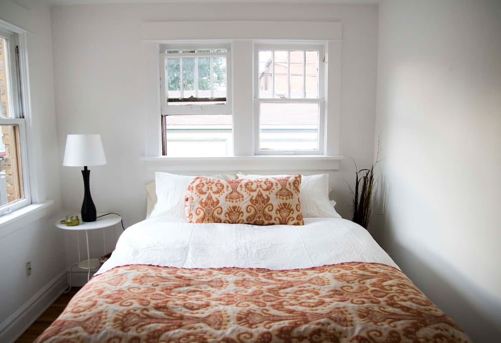 Queen-sized bed in the bedroom with custom-made throw and pillow covers