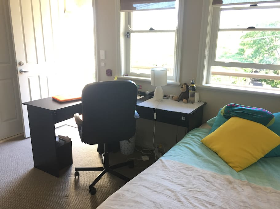 The room has a fan, wardrobe, study desk, chair and balcony.