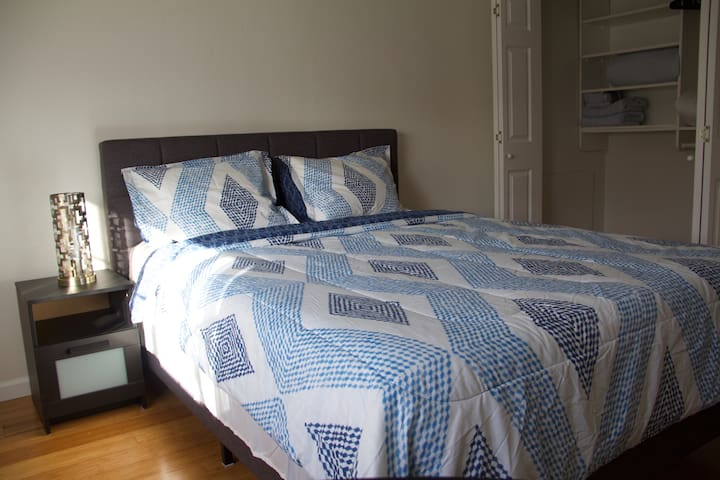Brand new queen bed with bedside table and bedside lamp.