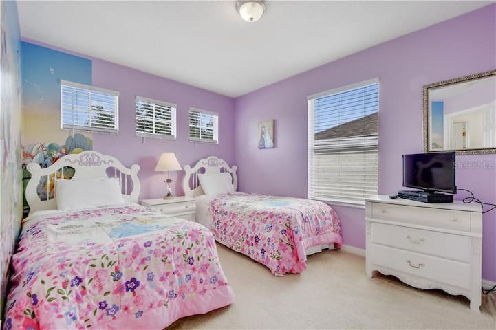 This Princess themed room features twin beds and a flat screen TV  The twin bedrooms share a bathroom which offers a shower, bath tub, sink and toilet