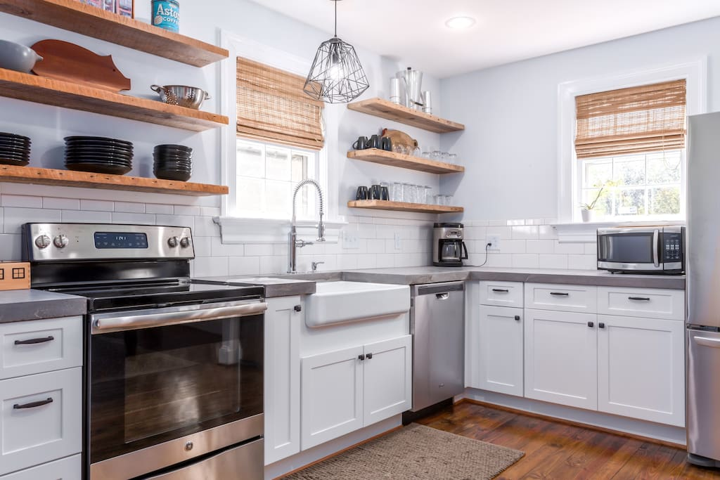 Modern kitchen has been stocked with all of the essential tools including pot, pans and service for eight.