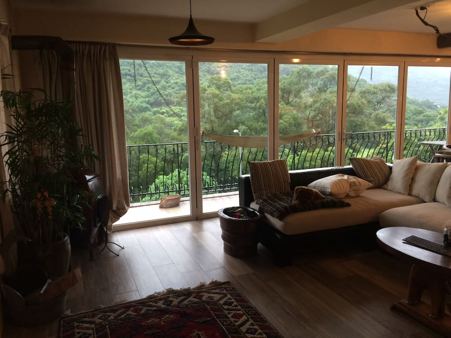 The living room and kitchen windows open completely for a beautiful green view