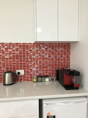 New kitchen with electric frypan, microwave and coffee machine.