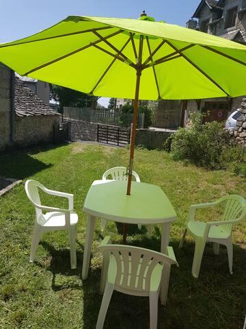 jardin avec table et chaise de jardin , parasol et barbecue au charbon