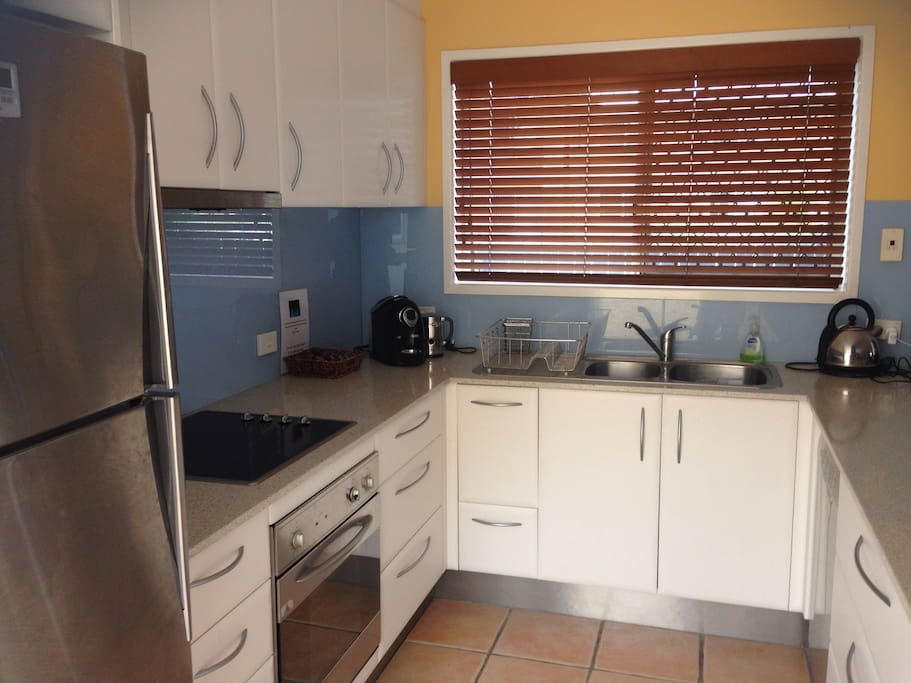 Fully equipped kitchen with oven, stove, microwave, dishwasher, coffee machine and full sized fridge