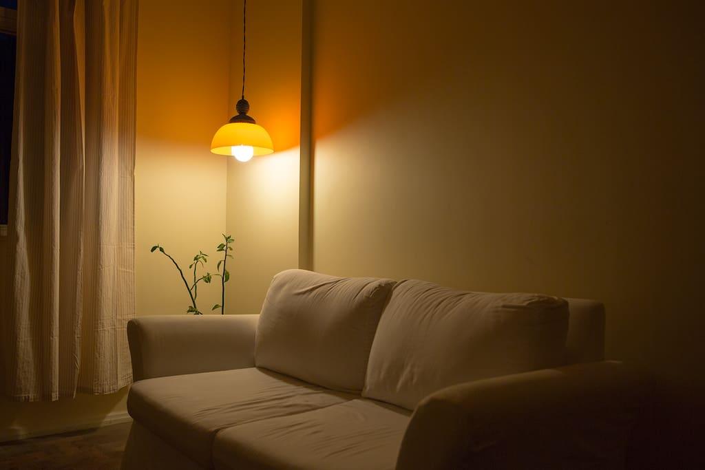 Sala com pequeno sofá e espaço para acomodar um casal em colchão de casal disponível no imóvel