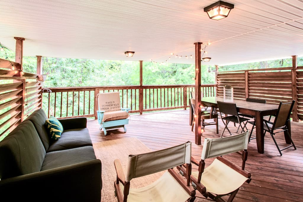 Large covered deck overlooks serene wooded backyard