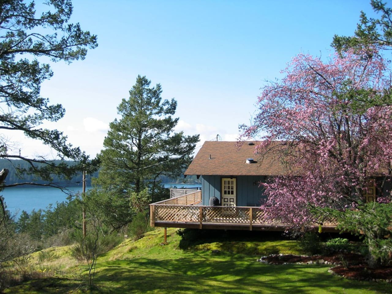 From Orcas Hill House there's a view of the ferry landing and boat traffic. The one-level home is perched on natural moss and lichen covered outcoppings, surrounded by decks and madrona trees.