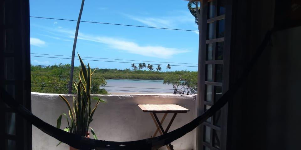 Foto tirada da sala de estar, onde há uma varanda que ilumina e ventila a casa com a brisa marinha.