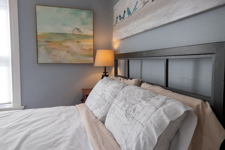 The bedroom features a queen bed with memory-foam topped mattress, a nightstand, bookshelf, and full-length mirror.
