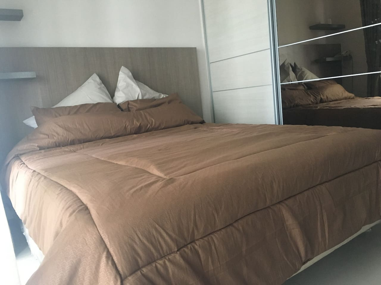 Queen size bed with puffy bedcover and pillows
