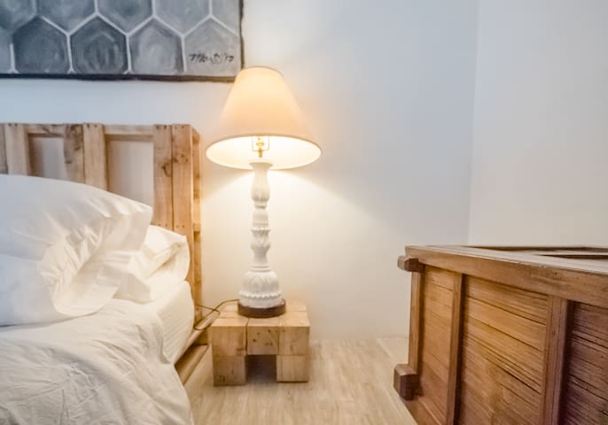 Beds and side tables made from repurposed shipping pallets. Surfaces are provided for your bags