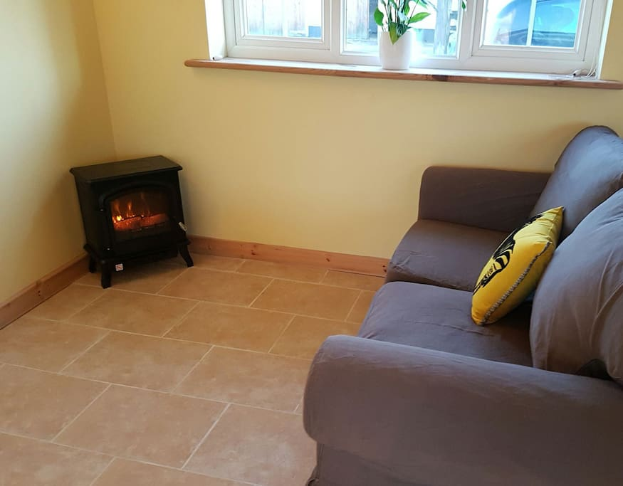 """The seating area and electric """"woodburner"""" in the bedroom."""