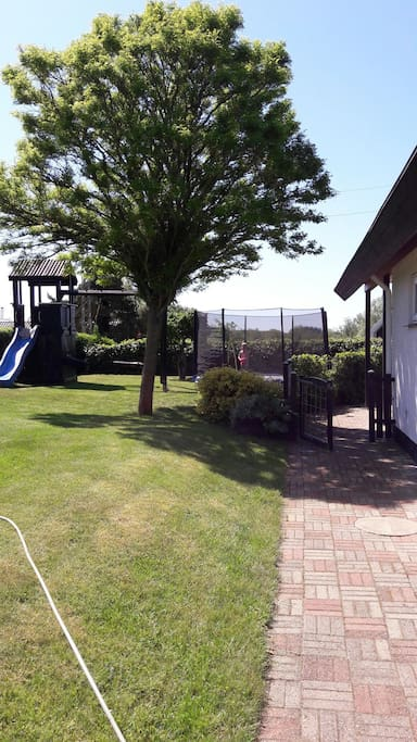 skøn lukket have med legetårn og trampolin