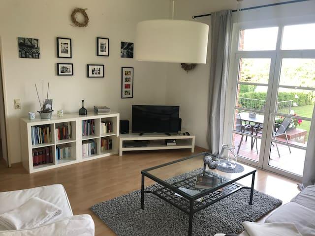 Wohnzimmer mit Zugang zur Terasse und Flat-TV