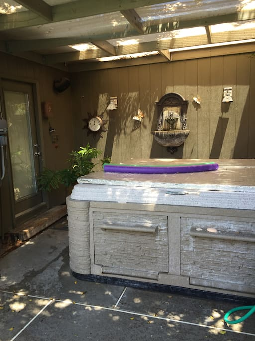 Hot tub right next to guest house in backyard by pool