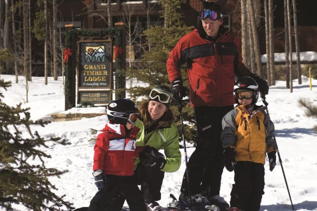 Ski-In and Ski-Out.  Strap on your skis from and hit the trails right out from the resort.  You can see the Grand Timber Lodge sign there where this family is about to Ski-Out for the day.