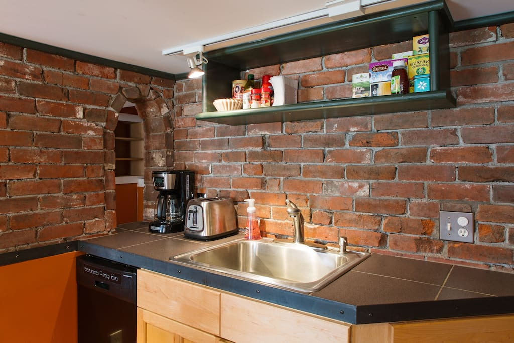 Exposed brick in the kitchen and a small but mighty dishwasher.