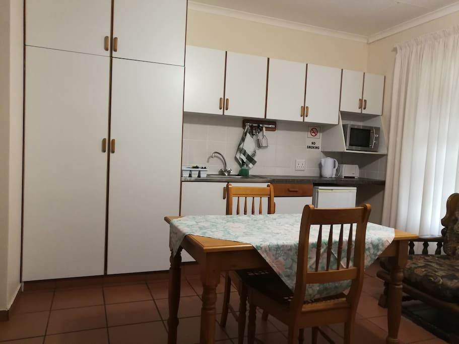 Kitchenette with stove, microwave, Bar fridge, crockery & cutlery