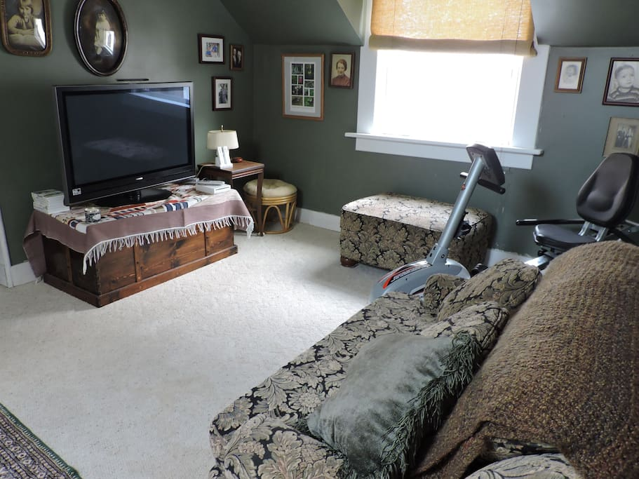 Upstairs living area with recumbent bike and TV.