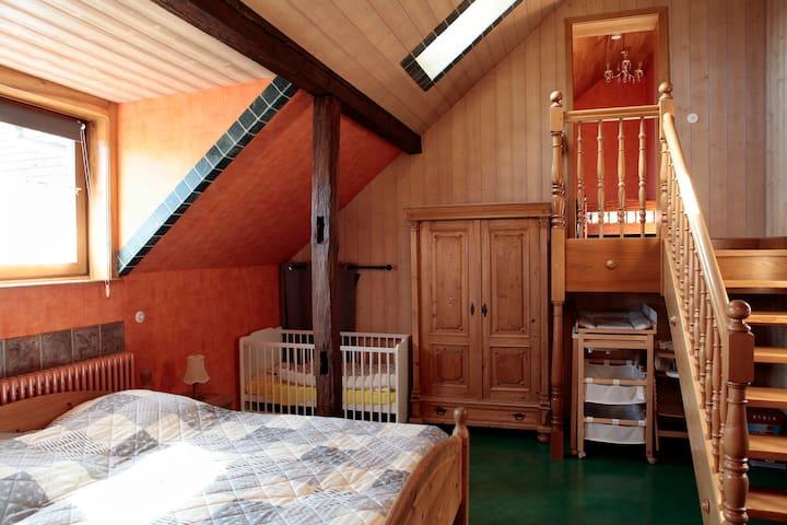 """Schlafzimmer mit Doppelbett, Kinderbett und Aufgang zum """"Kinder""""zimmer"""