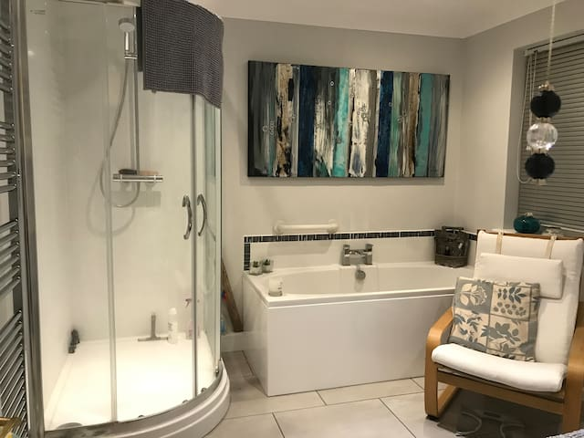 Modern bathroom with a large dual power shower and large bath.Toilet. Shaver point
